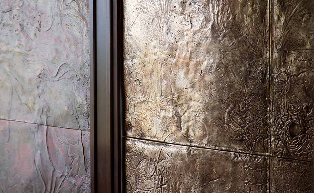 19. Dekoratyvinės sienų plokštės reljefiniu paviršiumi padengtos bronza.