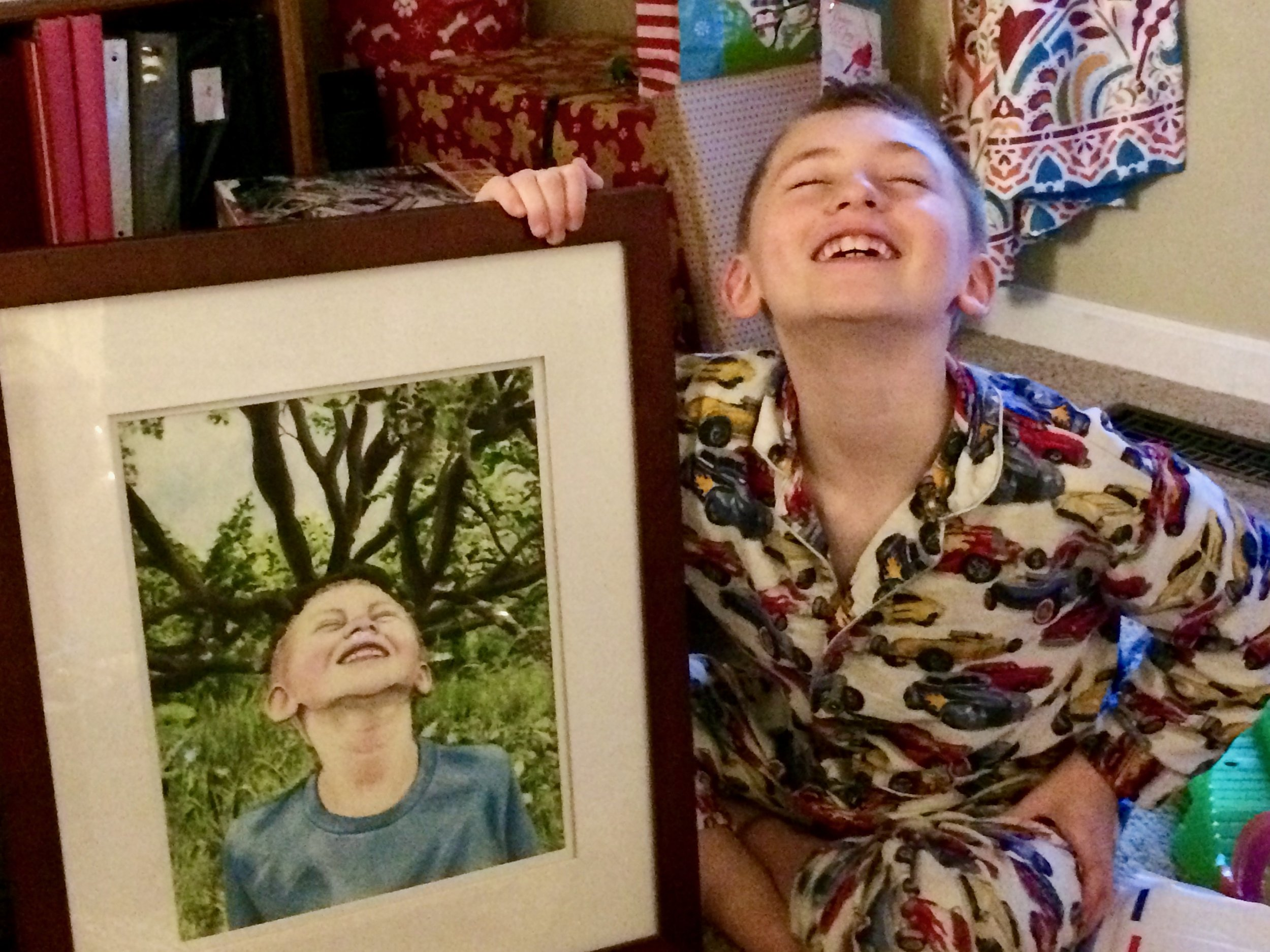 My nephew posing on Christmas morning with the portrait of him I painted