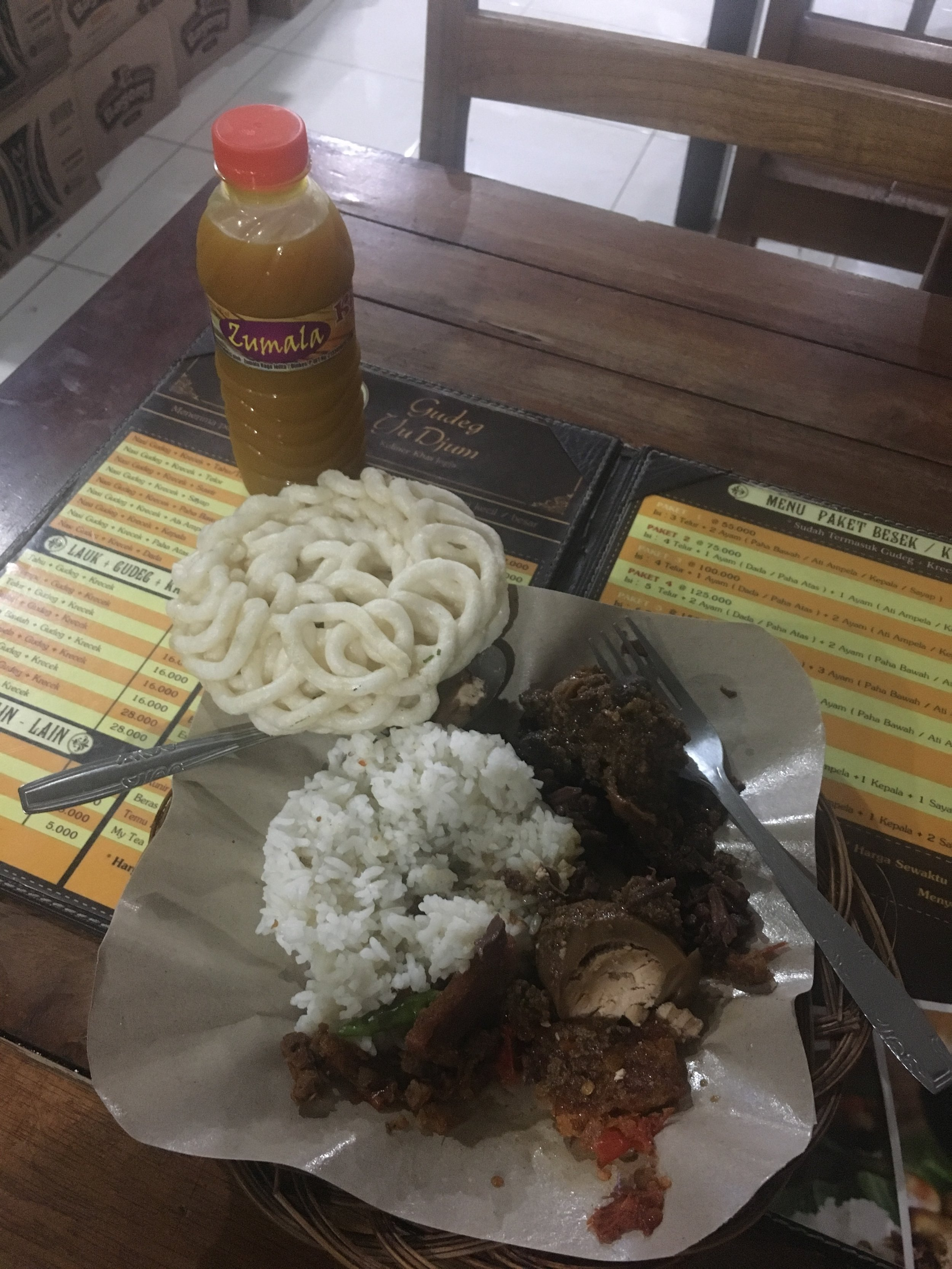 Gudeg with chicken liver, hard boiled egg, rice, and a local drink.