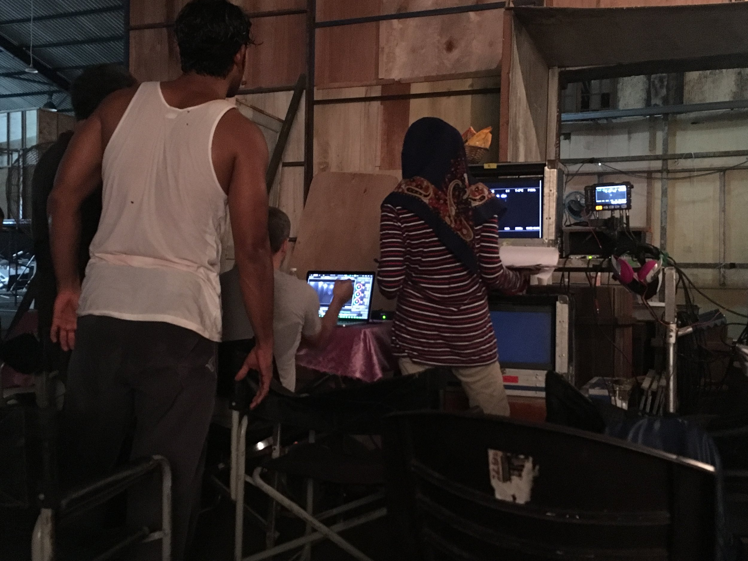 The star of the movie is the man in the foreground wearing a white tank-top. They are reviewing the scenes that were just filmed.