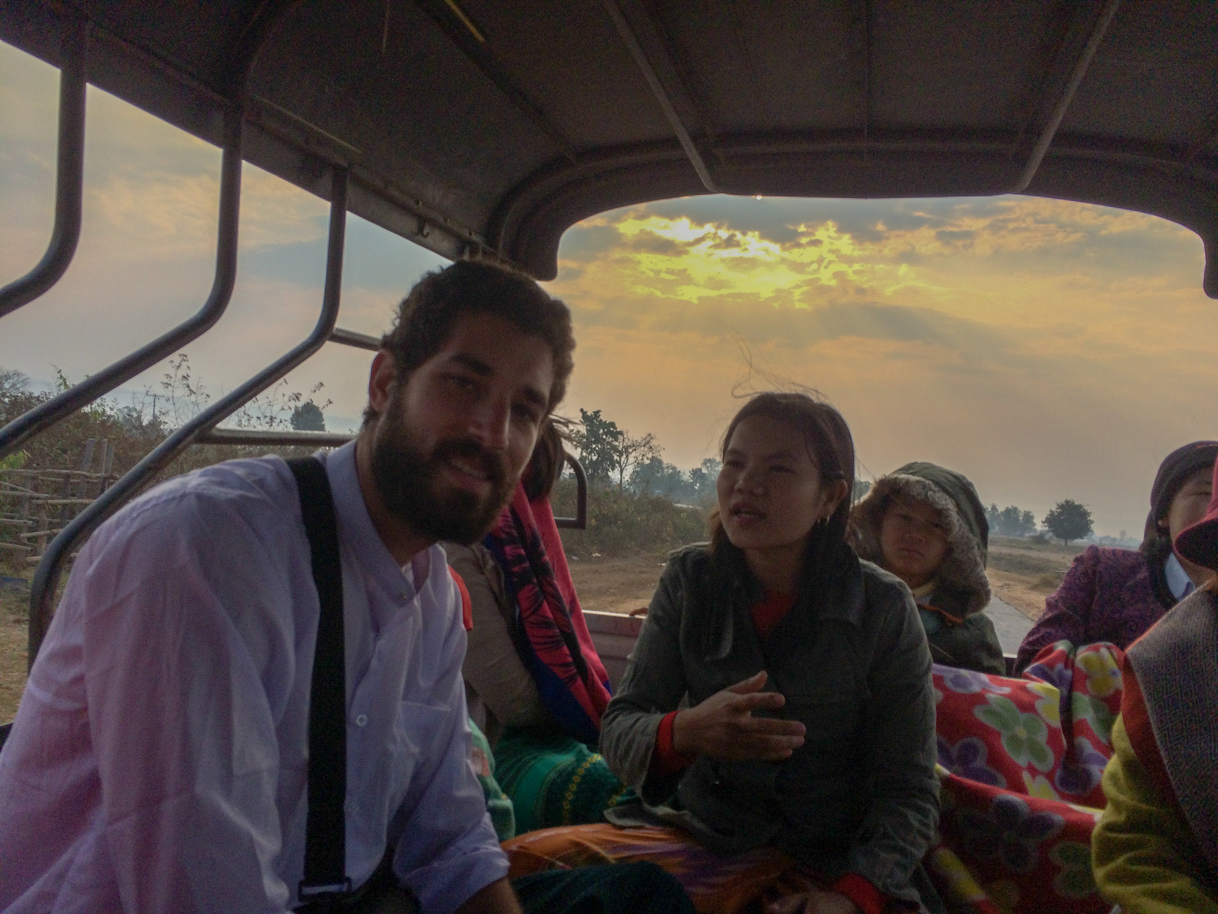 Riding in the back of a pick-up with a family in Myanmar for a two hour ride along unpaved roads.