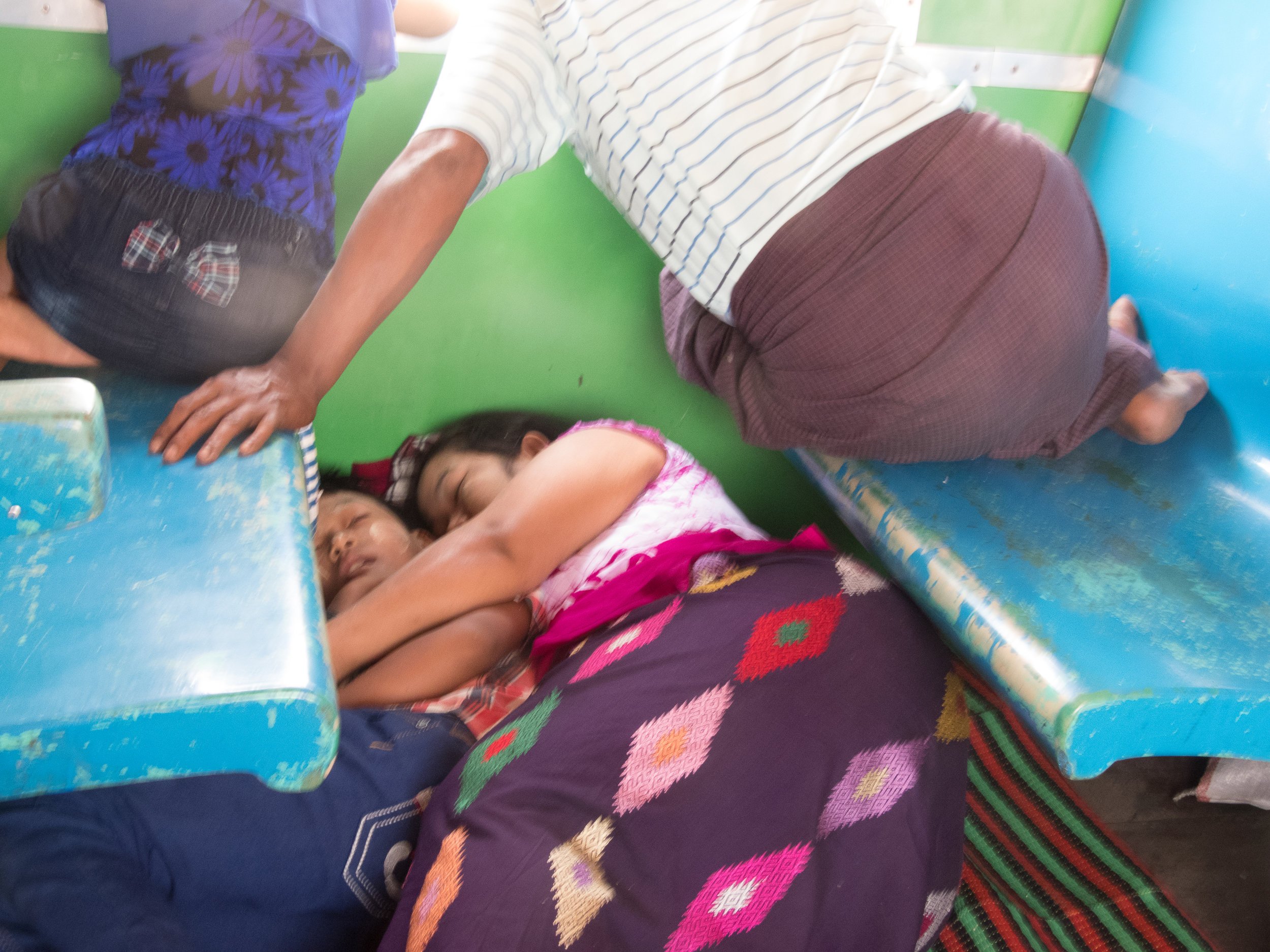 Family and friends are affectionate towards each other in Myanmar. Here, the mother and son sleep below the seats.