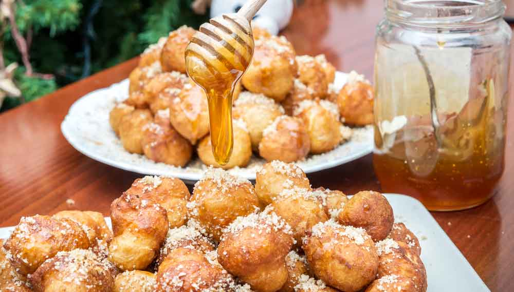 LoukoumadeS  light, airy, puffs of fried dough drizzled in sweet syrup and sprinkled with chopped walnuts