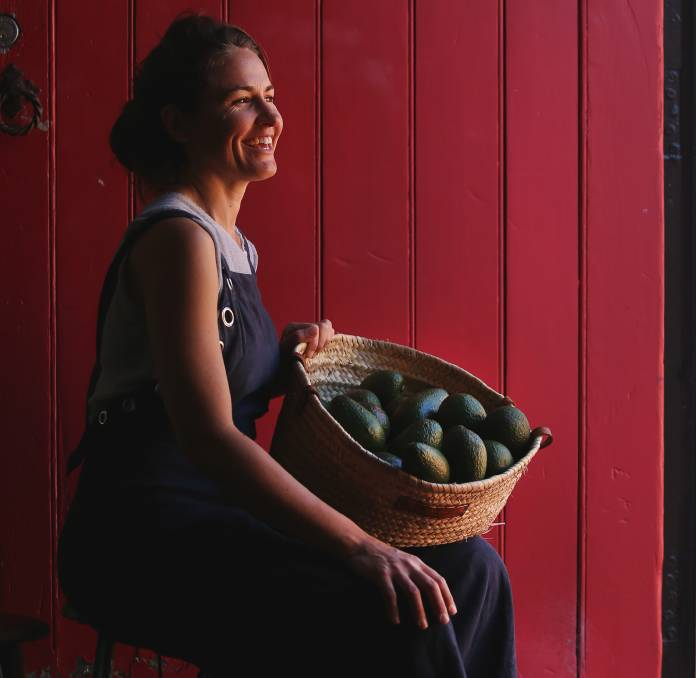 """A fan of good food: Bec Bowie, owner of Estabar, with some Sandy Hill avocados, at her home in Newcastle East. As she says: """"When you say no to gassed or cold storage fruit and veg, you just get what nature gives you. We think that's ok. This means sometimes we don't have ripe avocados and it means we always treat them each one of them as precious."""" Picture: Marina Neil"""