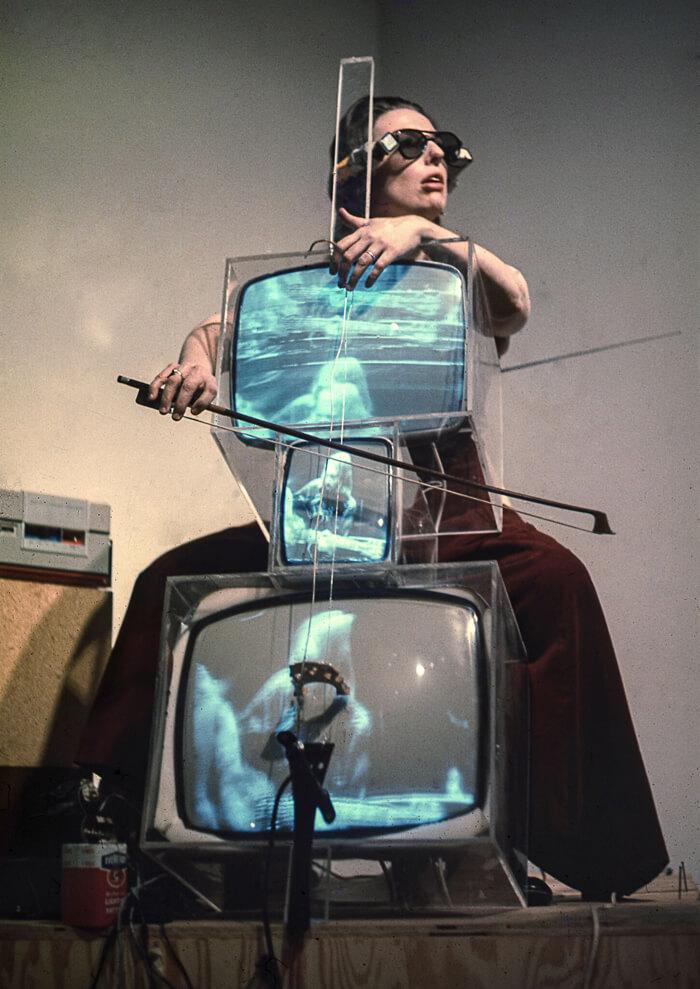 Charlotte Moorman performing on Nam June Paik's TV Cello wearing TV Glasses, Bonino Gallery, New York City, 1971   Photo: Takahiko Iimura. © Takahiko Iimura