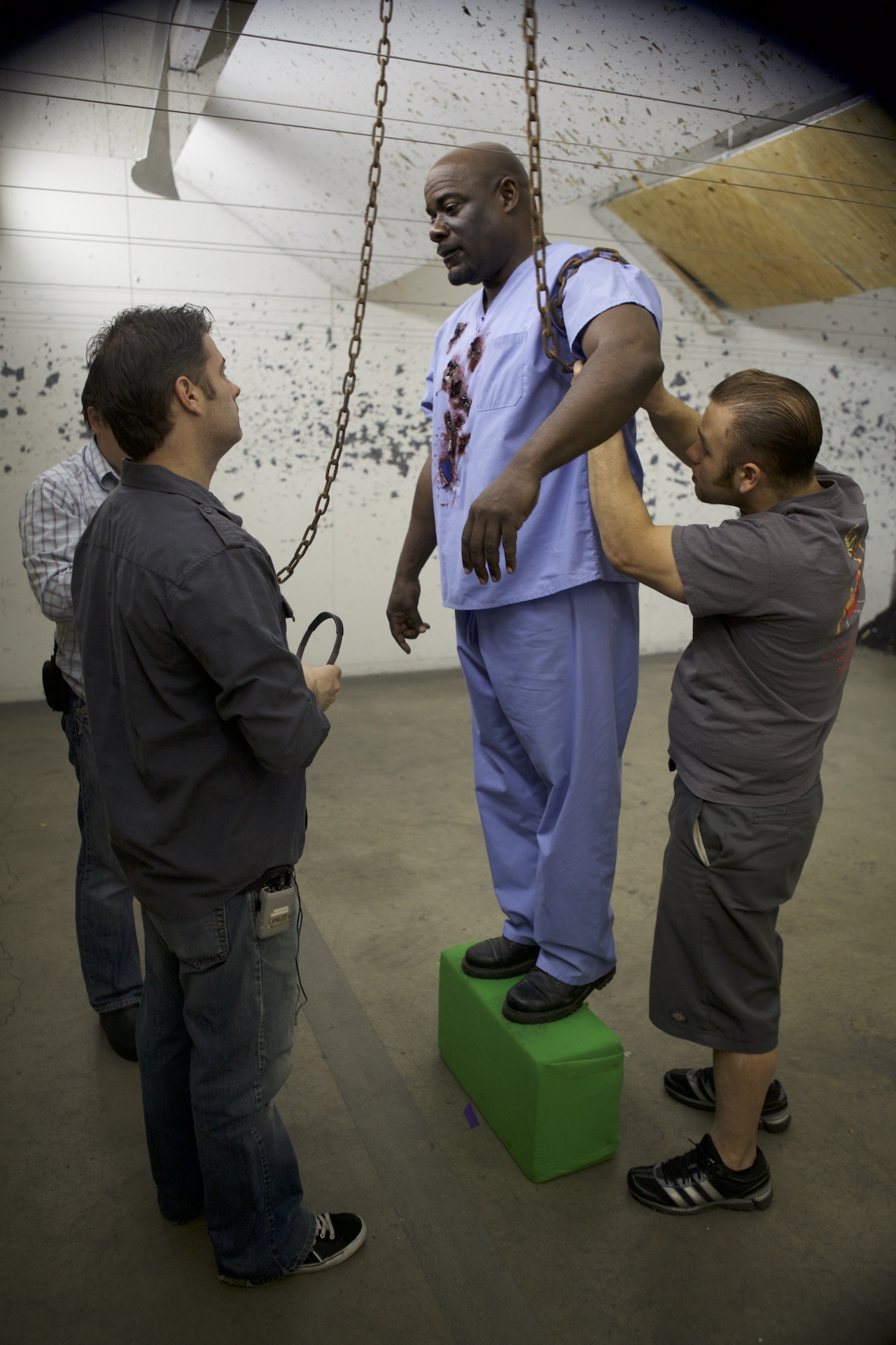 Giving a note to actor a'Ali-Salaam while the prop guys secure him for the scene. Firing Line gun range, Burbank. Spring 2011. Photo by Scott Everett White.