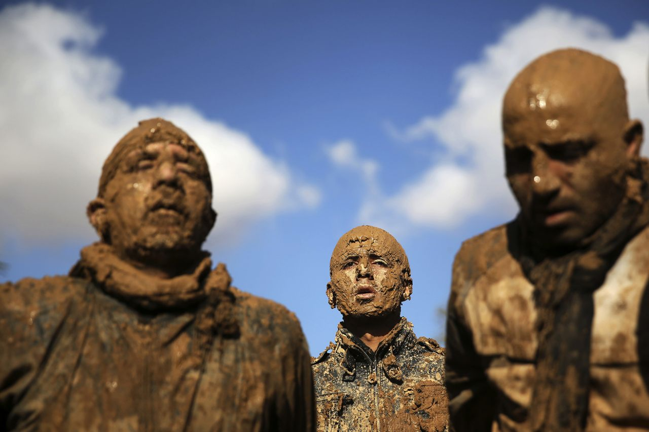 Iranian Shiites cover themselves with mud during Ashoura, marking the death anniversary of Imam Hussein, the grandson of Islam's Prophet Muhammad, at the city of Bijar, west of the capital Tehran, Iran, Nov. 14, 2013. (Photo: Ebrahim Noroozi/AP)