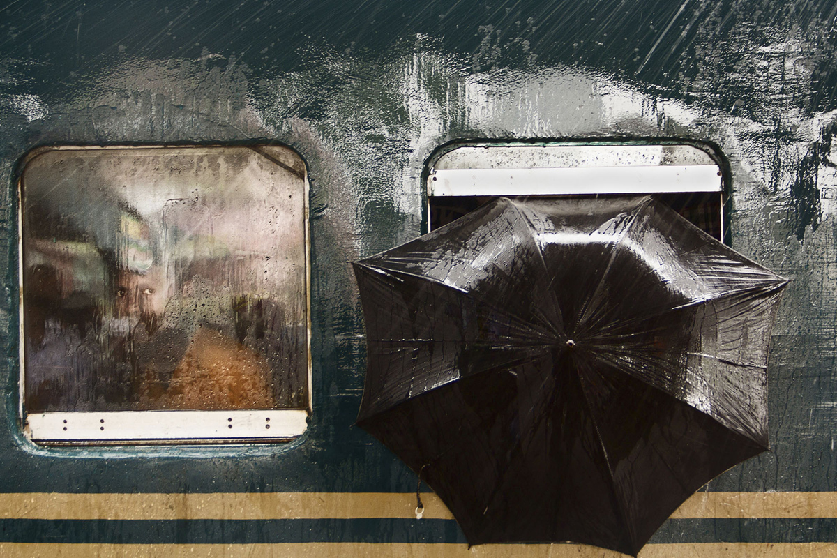 The Man's Stare - Honorable mention, People. The photo was taken on July 23rd 2016 at Tongi Railway Station in Gazipur, Bangladesh. I was there taking photos and waiting for a moment. A train from Dhaka toward another district stopped at the platform for 5 minutes for lifting passengers. It was raining a lot. Suddenly I found a pair of curious eyes looking at me through the window and on his left an umbrella has been put to protect from the rain. I got the moment.