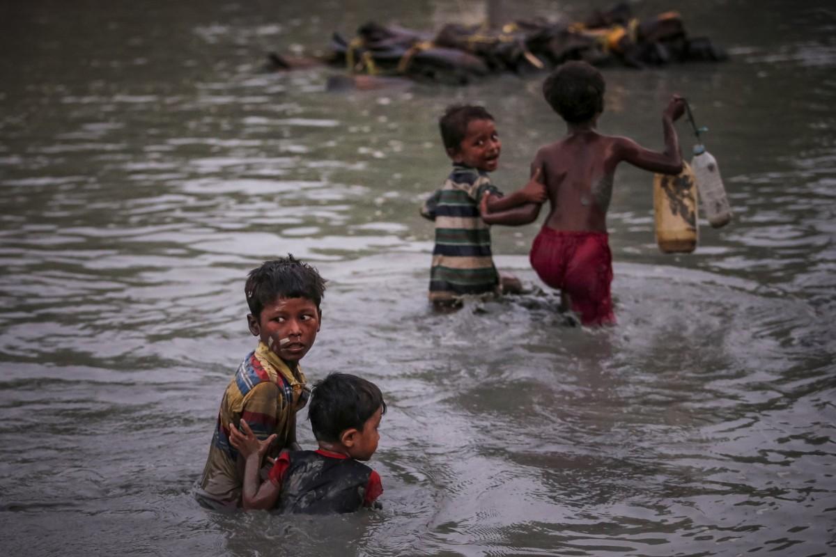 Rohingya siblings fleeing violence hold one another as they cross the Naf River along the Bangladesh-Myanmar border in Palong Khali, near Cox's Bazar, Bangladesh, November 1, 2017. (photo from Pulitzer.org)