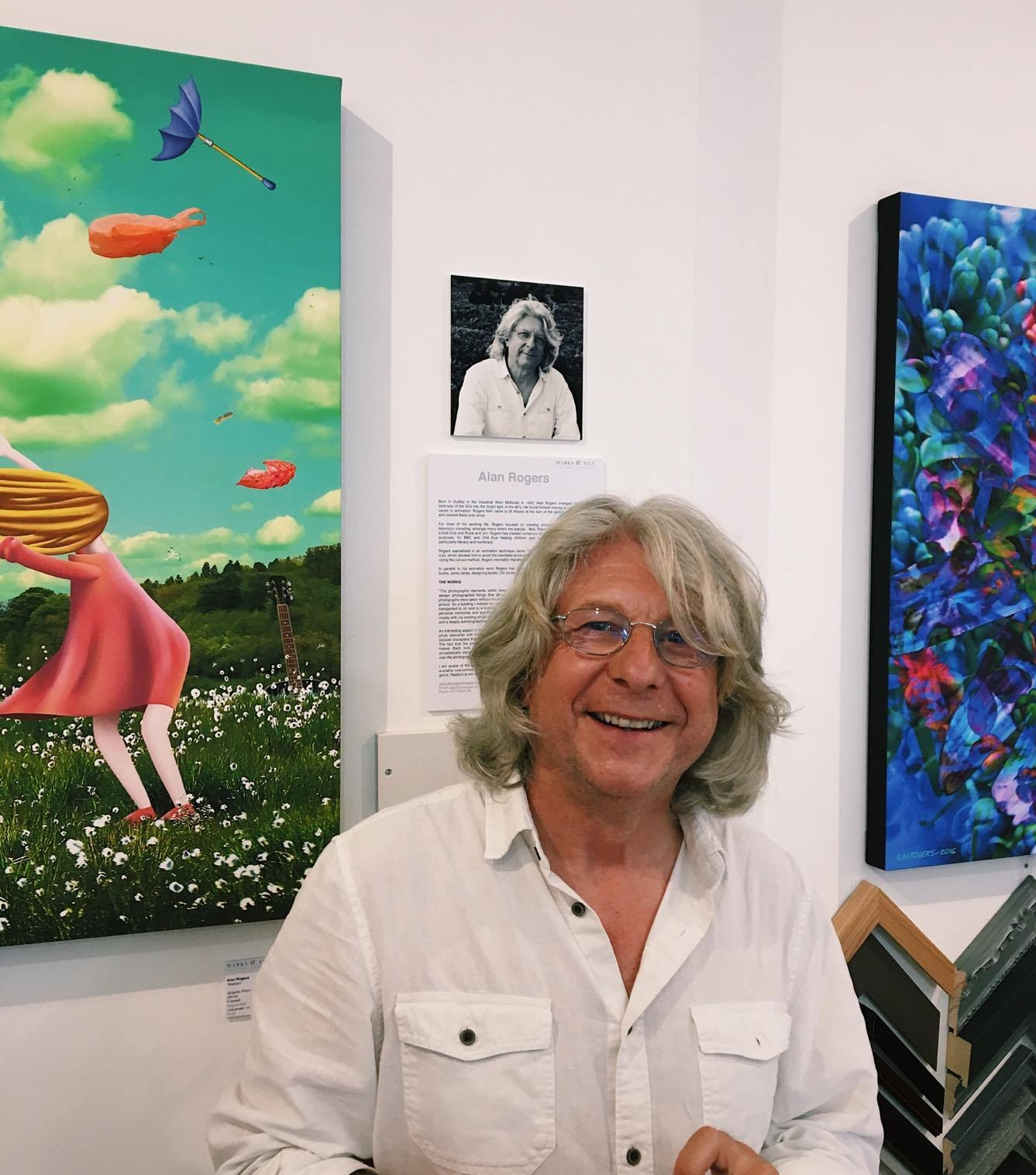 """Alan Rogers7th - 25th July 2017 - Born in Dudley in the industrial West Midlands in 1952, Alan Rogers emerged from the darkness of the 50's into the bright light of the 60's, He found himself moving to London for a career in animation. Rogers then came to St Albans at the turn of the century and has lived and created there ever since.For most of his working life, Rogers focused on creating animated films for children's television, including, amongst many others the popular - Bod, Pigeon Street, The Flumps, Rub-a-Dub-Dub and Rosie and Jim. Rogers has created numerous children's films, for educational purposes, for BBC and Ch4 thus helping children gain insights to many subjects but particularly literacy and numeracy.Rogers specialised in an animation technique called """"Cut-Out Animation"""" Working with cut-outs, which allowed him to avoid the inevitable production line aspect of the animation process. Using the cut-out method, Rogers inevitably migrated his whole practice onto computer.In parallel to his animation work Rogers has also illustrated (and often written) children's books, comic strips, designing books, CD covers, logos, character design, and photography.""""The photographic elements within these pieces are autobiographical by definition. I have always photographed things that attract my attention as I go about my life. Most of the photographs were taken without me being aware that they would later end up incorporated in a picture. So a building I noticed ten years ago in a particular place and time, could be lifted and transported to sit next to a building I noticed only two weeks ago. Both buildings would have personal memories and significance to me beyond their simple bricks and mortar. Working mostly with my existing photo archive limits the possibilities but adds an element of serendipity and a deeply autobiographical note to each picture.An interesting aspect of this process for me is experimenting with various ways to combine the photo elements with the """