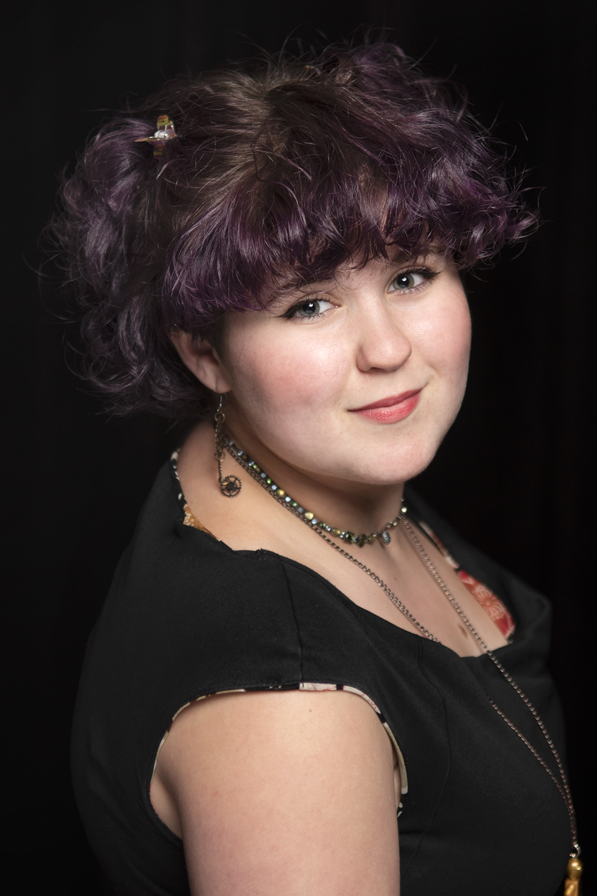 Actor Headshot for Spring Theatre, located in Winston-Salem, North Carolina | Photographed by Jasper & Fern | Winston-Salem photographer | Traditional Headshots | Actress Headshots | Thespian headshot | All black headshot backdrop | purple hair style | short curly hair style