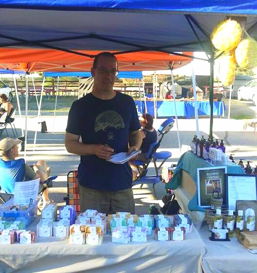 Whole Life Soaps' Owner, Bill McConnell selling soaps and lotions at a local farmer's market.  Photo Credit: Laurie McConnell