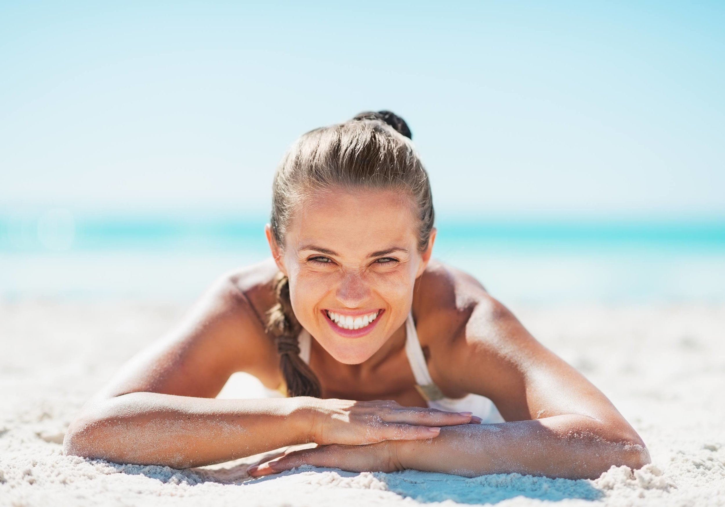 smiling-young-woman-in-sunshine-on-beach.jpg