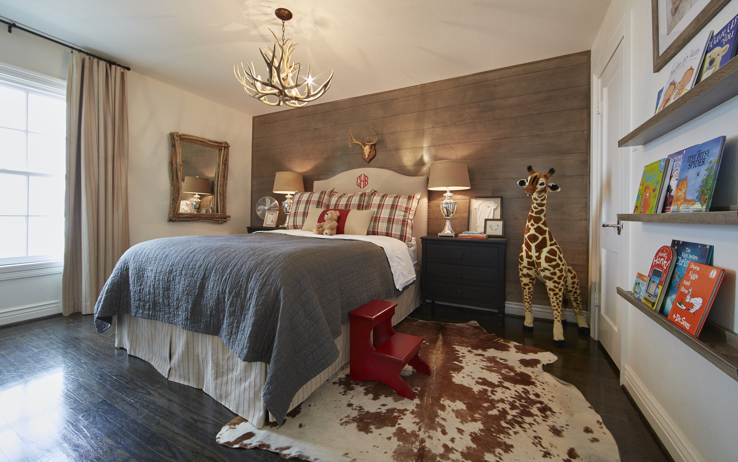 Son Beckham's room features a more rustic take on farmhouse styling with its stained shiplap wall, antler chandelier and cowhide rug. Emily chose red accents to reflect his fiery personality.