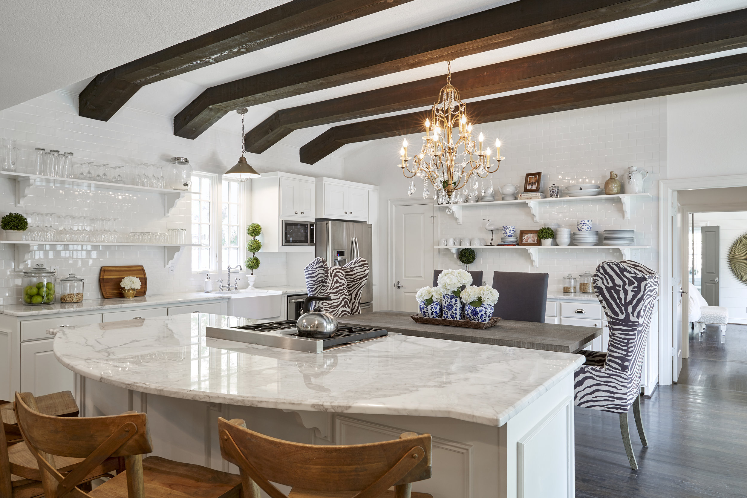 Dark ceiling beams  and wood floors add texture and visual interest to the stark white kitchen.