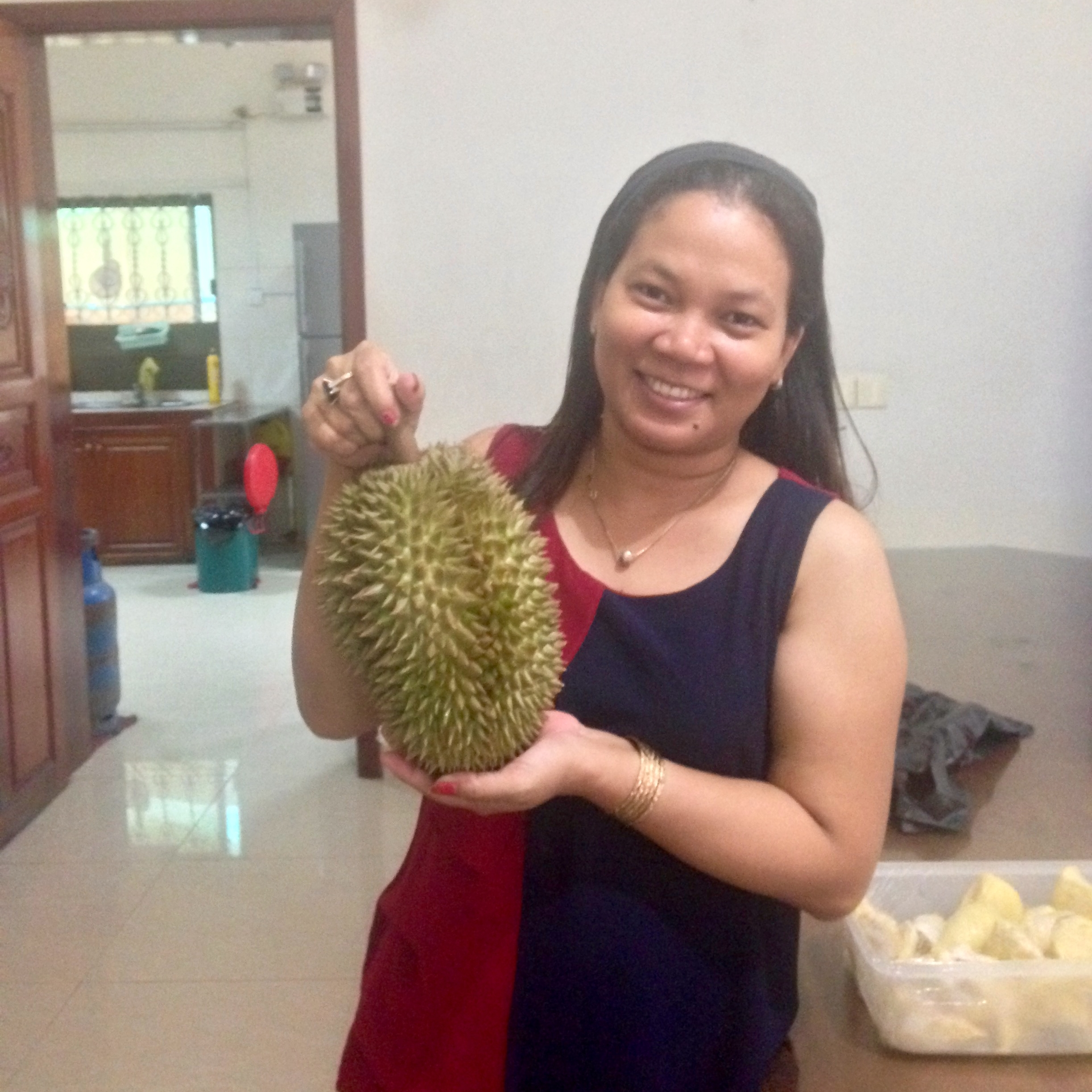 Avy holding a durian, a popular fruit in Southeast Asia with a rather pungent scent
