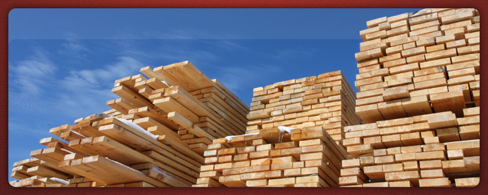 dimensional cut lumber stacked up in winter high into the blue sky