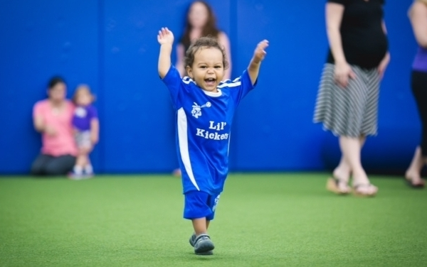 picture of a toddler playing soccer and celebrating a goal.