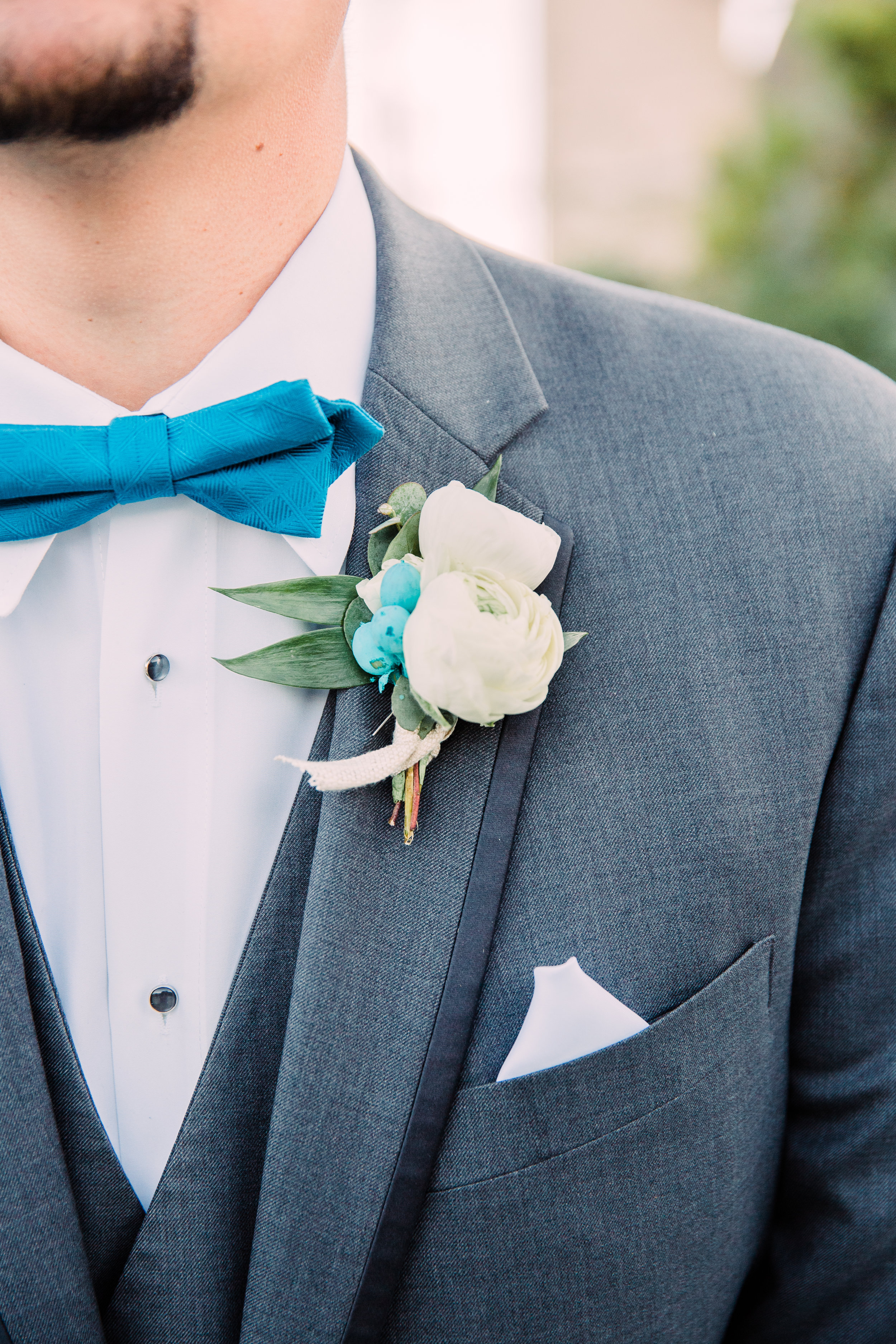 Adorable little blue bow tie with a beautifully complementing boutonnière. I simply adore the splash of matching blue underneath the white flowers.
