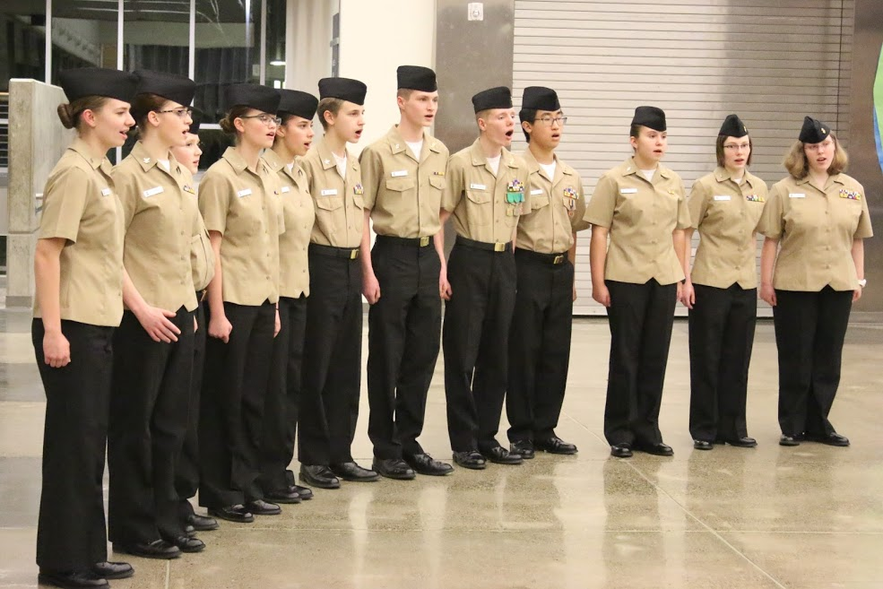 The Patriot Company Choir, Led by Cadet Petty Officer Third Class Elise Fosmark (second from left), sings the National Anthem to open the ceremony.
