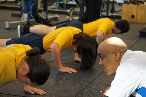 Naval Science Instructor, Chief Spears, provides a little motivation to Cadet Emily Lew as she struggles to complete more push-ups during the physical fitness competition.