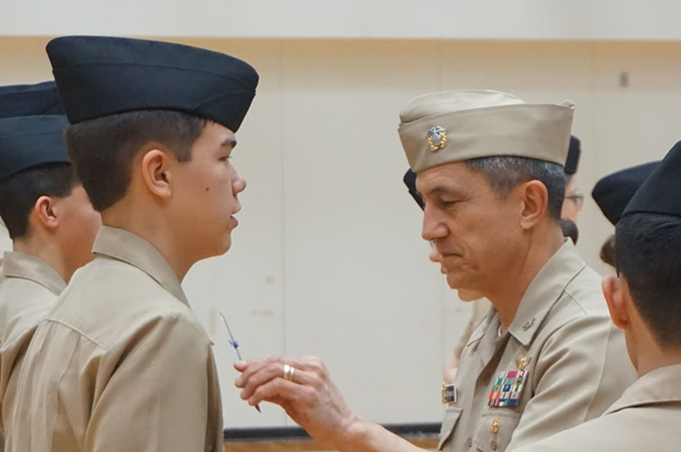 Captain Wenceslao measures the distance of Cadet Julius Sjolie's (9) rank device on his shirt collar to ensure it is in the proper position.
