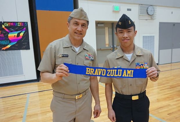 Cadet Commanding Officer Alex Pham (12) receives the Bravo Zulu Pennant from Captain Wenceslao upon completion of the Area Manager's Inspection.