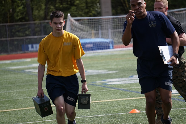 Chief Spears supplies some motivation as Cadet Matthew Martin runs the last 50 yards of the maneuver under fire portion of the Marine Corps Combat Fitness Test, while carrying two 35lb ammo cans.
