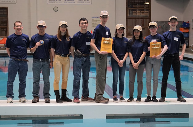 Captain Deehr (far left) poses with Patriot Company's Sea Perch Team after they won the Kitsap Regional Underwater ROV Competition on Saturday. Team members include from left to right: Cadets Timothy Caole, Faith Ellis, Dominic Ogino, Evan Rosenfelt, Kaitlin Lew, Mathea Caole, Sofia VanHuss, and Carson Tucker.
