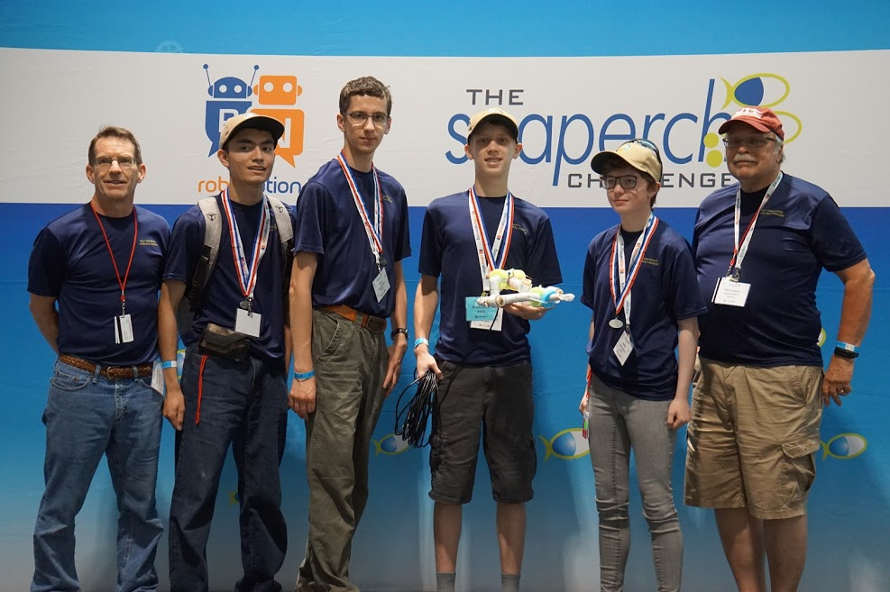 From left to right: Captain Deehr, Dominic Ogino, Evan Rosenfelt, Carson Tucker, Sofia VanHuss, and Mr. Dee Crouch prepare to have Patriot Company's underwater ROV checked by the judges prior to the national championship competition.