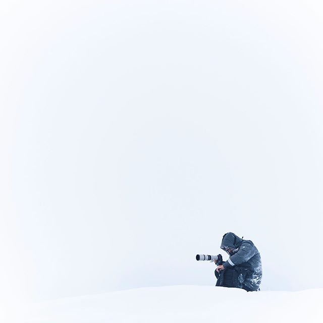 We were setting up at the majestic Fjallsárlón at the South end of the Vatnajökull glacier, when all of a sudden the conditions turned from serene and peaceful to a violent, bone-chilling blizzard. The stoke level basically exploded as many of us were howling at the storm, running around trying to fire off all kinds of bangers: dramatic mid-storm portraits, icebergs being swallowed by the snow, our modified Defenders getting whipped by the blizzard - really just firing off in any direction. In the midst of this craze I looked over to my right and saw @benjaminhardman, like a statue, completely immobile as he took a fat beating from the elements. Fully enthralled with his craft he seemed unaffected by the storm as he gently adjusted the focus on his camera. A great lesson from one of my favourite photographers to always commit and stay laser-focused on your shot even when the opportunities around you seem endless.
