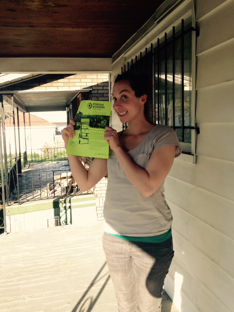 Liza Bielby holding a Porous Borders flyer
