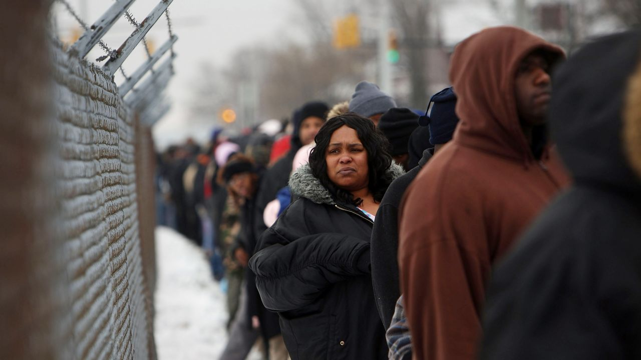 """People wait in a several-blocks-long line to receive food and gifts at the """"A Miracle in Motown"""" event, part of a nationwide program to help working poor. We've been here before."""
