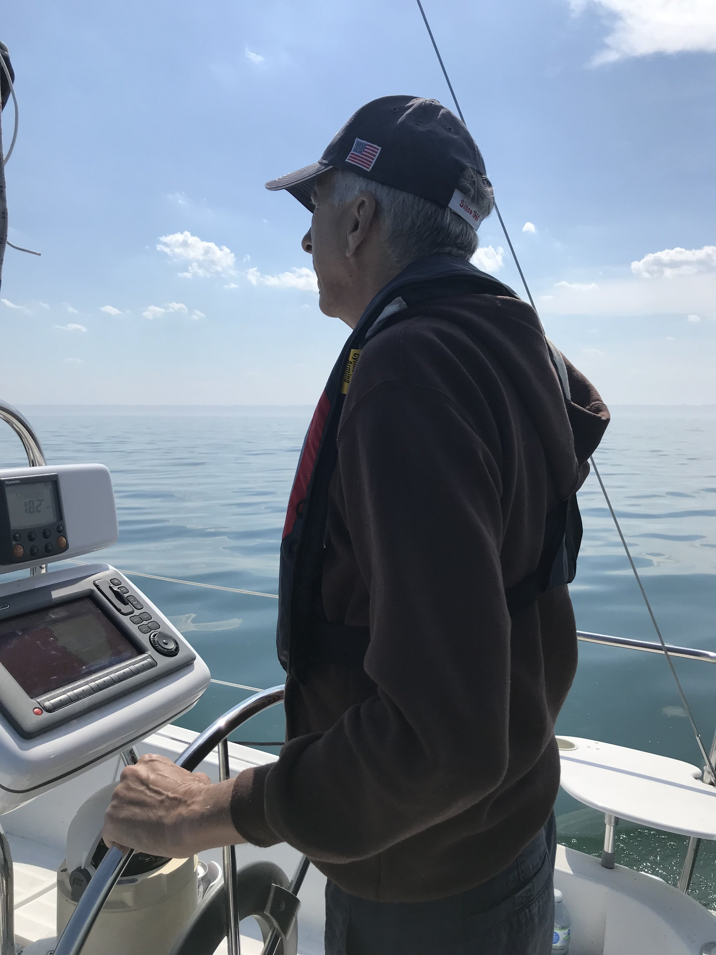 The author's father, Admiral Jim, at the helm of Knot Write.