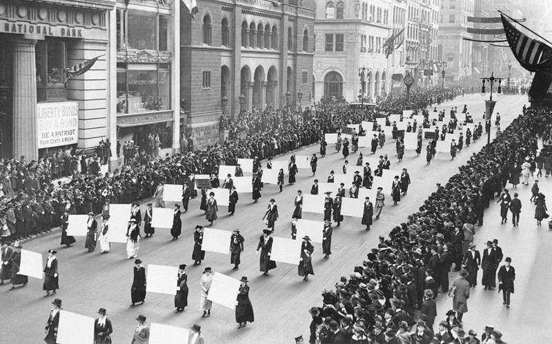 Suffragists parade down Fifth Avenue, 1917. Advocates march on October 1917, displaying placards containing the signatures of more than one million New York women demanding the vote. The New York Times Photo Archives.