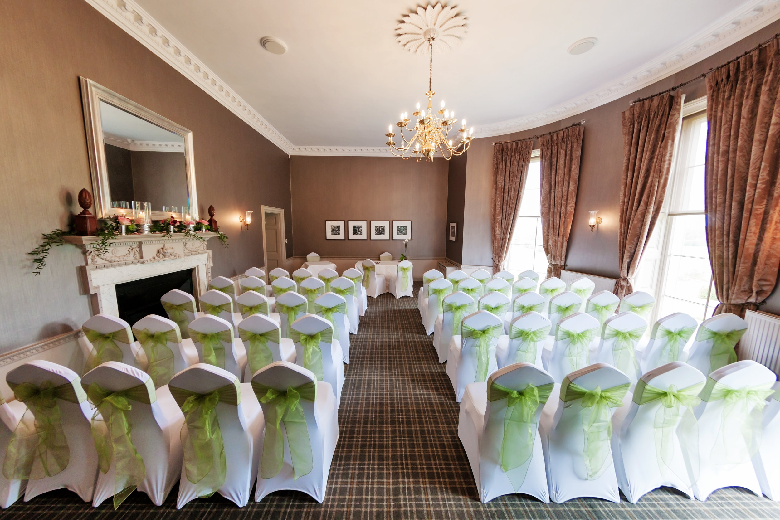 Length wise layout with long aisle and table at the far end of the room.