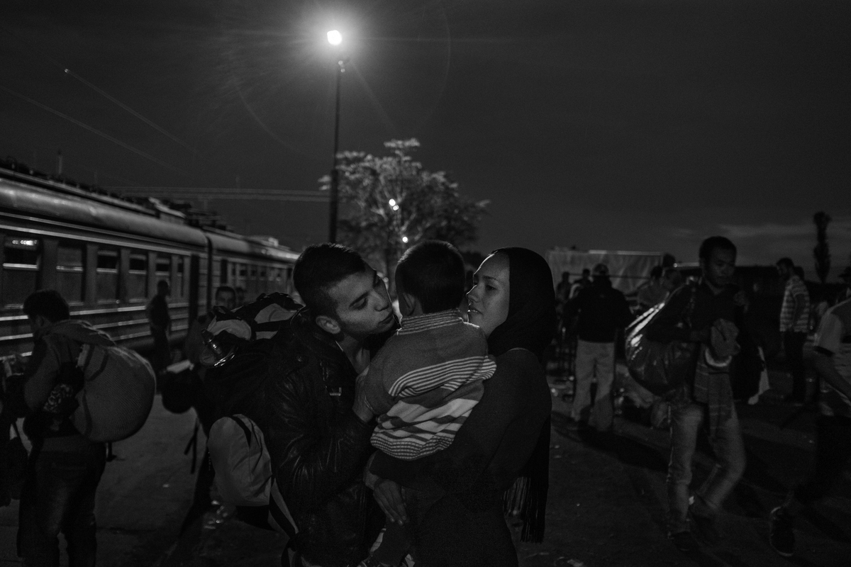 Mushawa Mosani-Akberi, 15, kisses his brother, Sajar, 1, being held by Razeer, a relative, before making his way to the Serbian border on October 4, 2015. Mushawa has been traveling from his home in Ghazni, Afghanistan for the past two weeks. He hopes to end his journey in France, where he dreams of becoming an architect. His parents could not afford the journey and remained behind in Afghanistan. The train, which is decades old and run down, takes five hours and costs each refugee, adult or child, €25.
