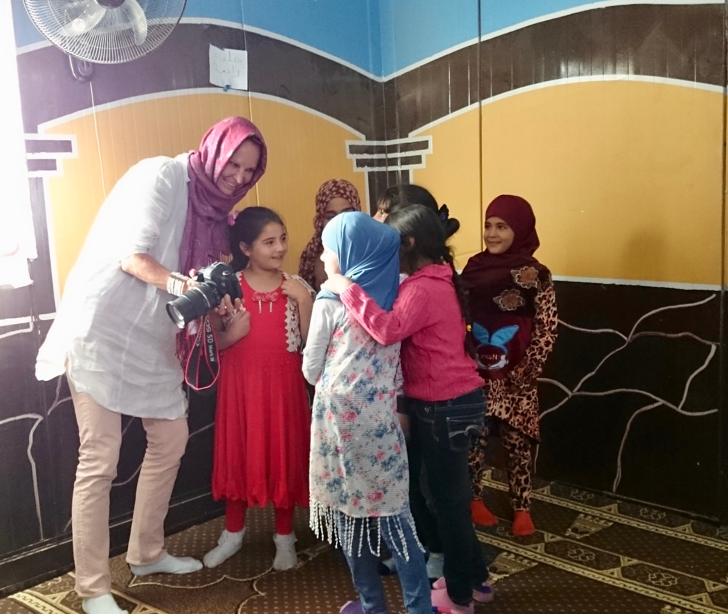 Sharing photos with young girls in the mosque in Village 6