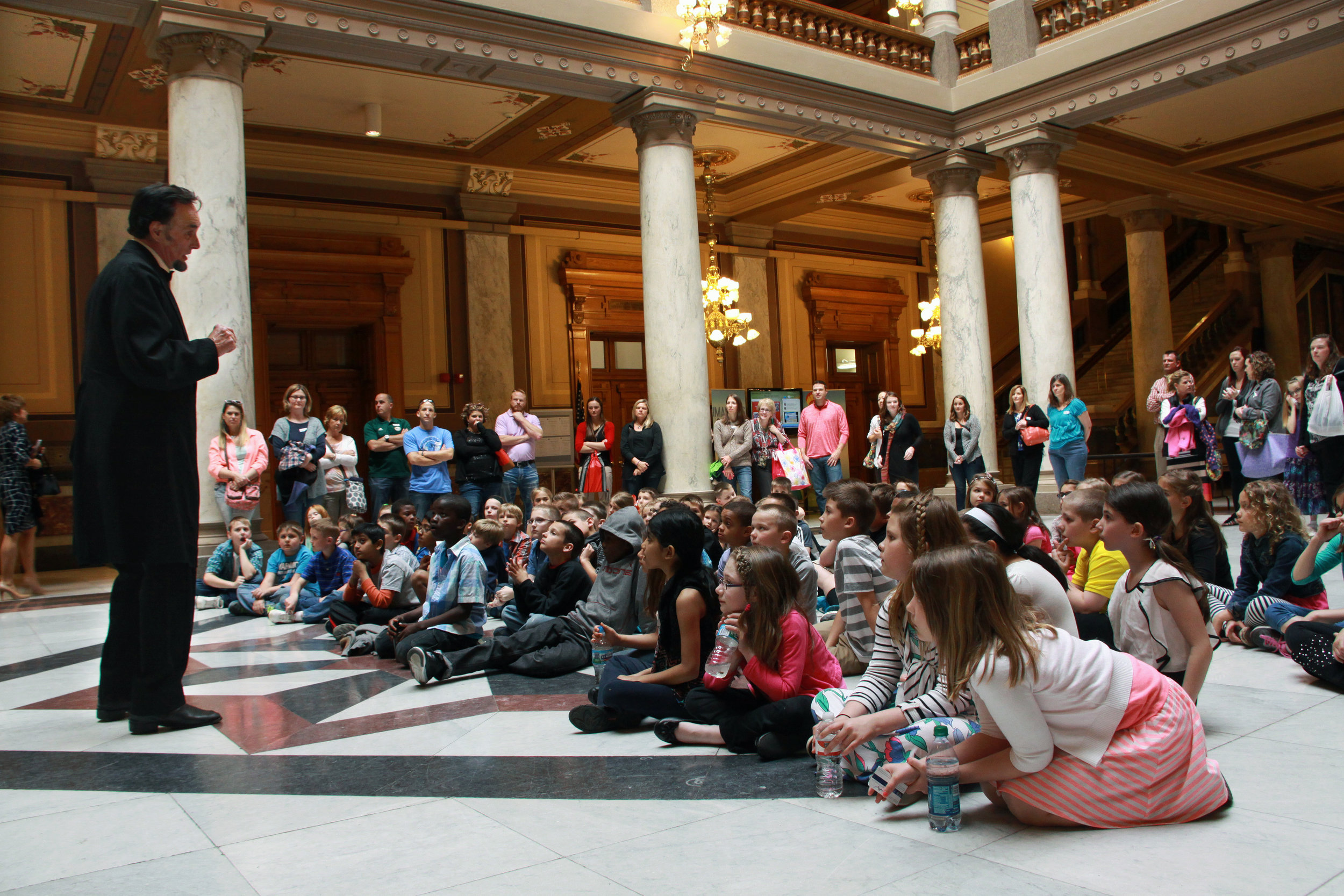 Children listen to President Abraham Lincoln reenactor in a courthouse lobby