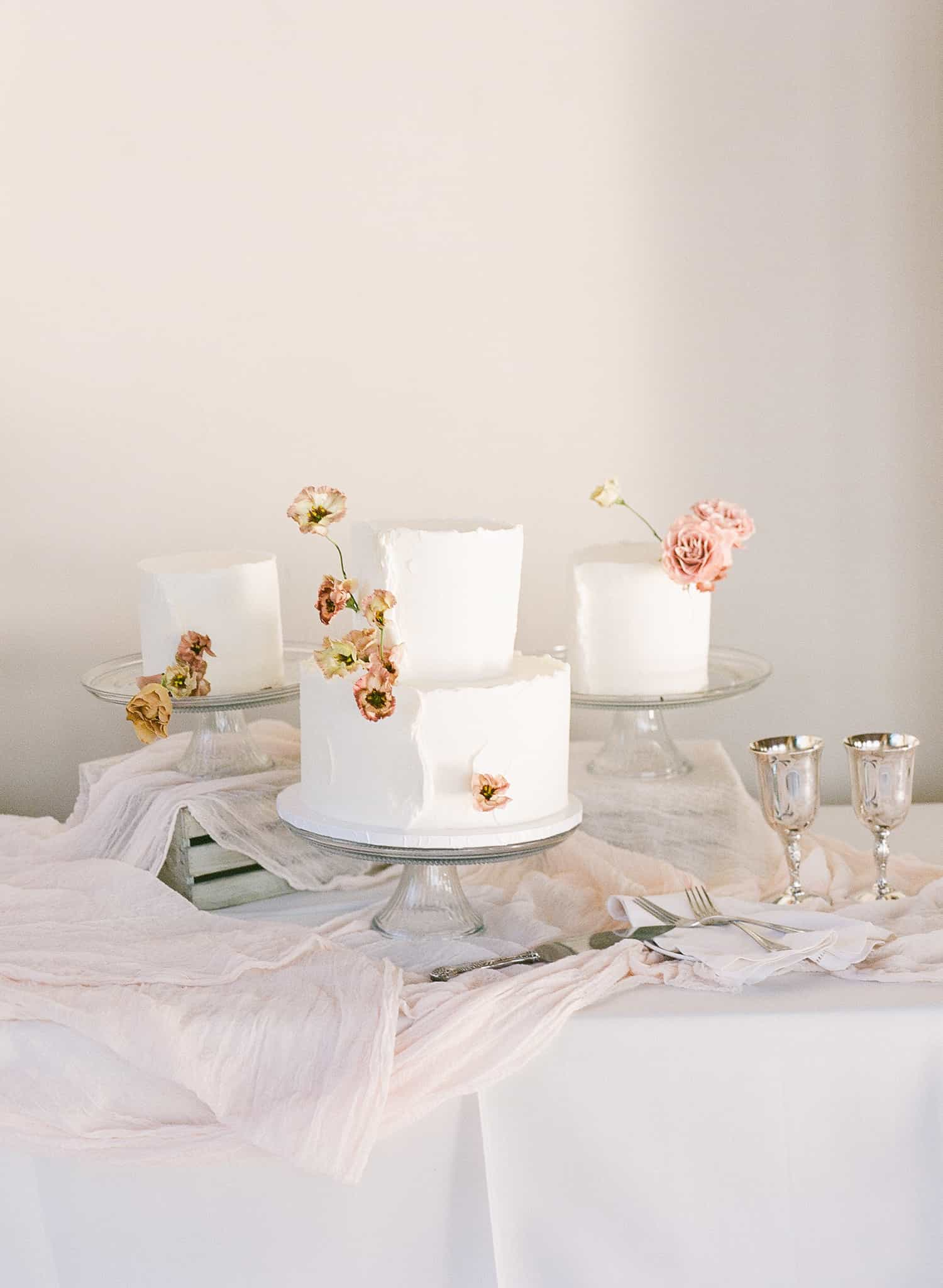 Wedding cake adorned with flowers by Color Theory Collective