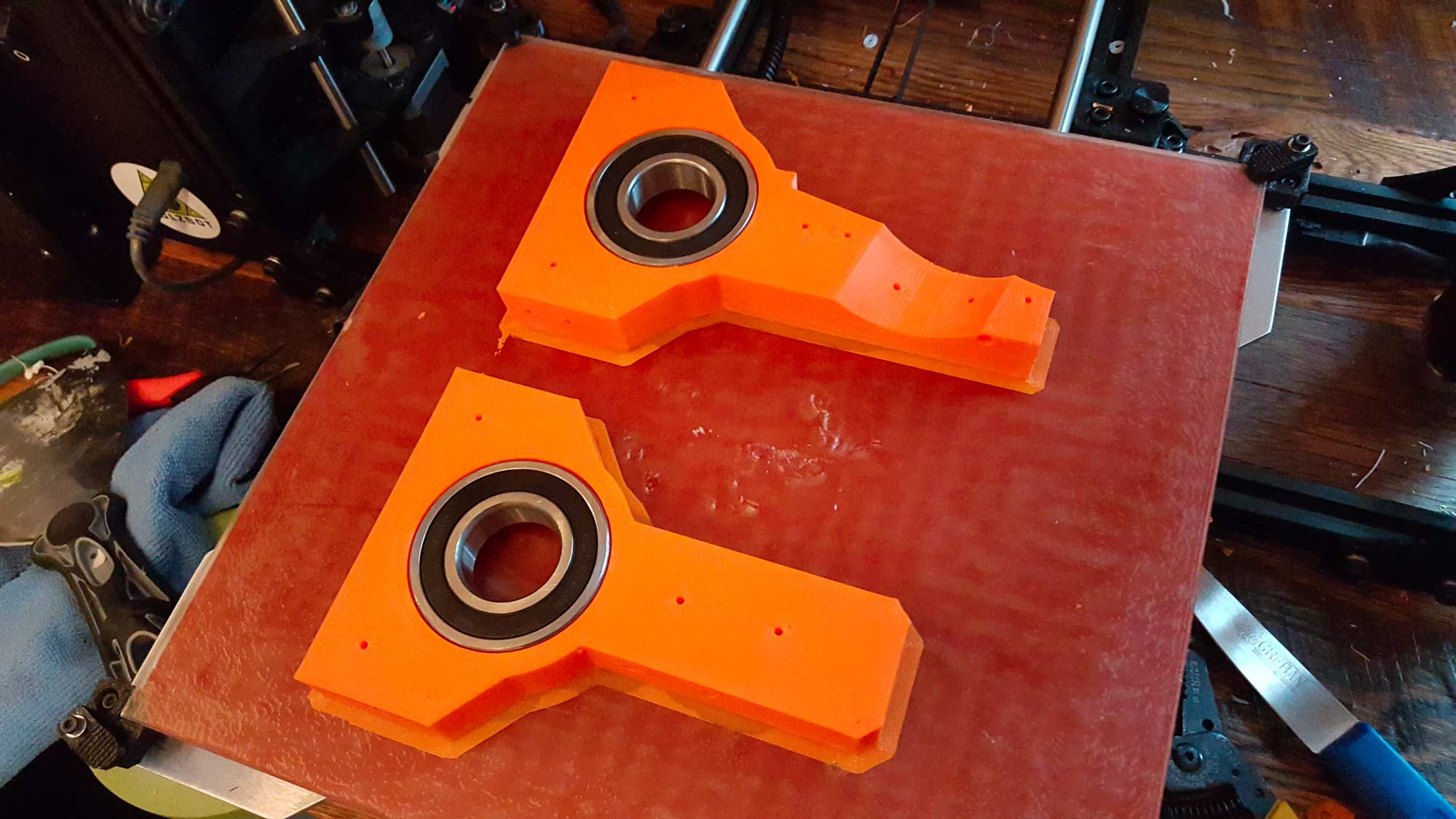 """This print I am super proud of and have to give myself a little pat on the back. I printed the """"trousers"""" which have a recess for a bearing that will go around main axis. As soon as the print finished I test fitted the bearings and thankfully they fit. Then the genius part....I decided to leave the bearings in the hot print on the bed. As the plastic cooled it contracted around the bearing and the bearings basically installed themselves. Those suckers are in there for good with no glue or anything."""