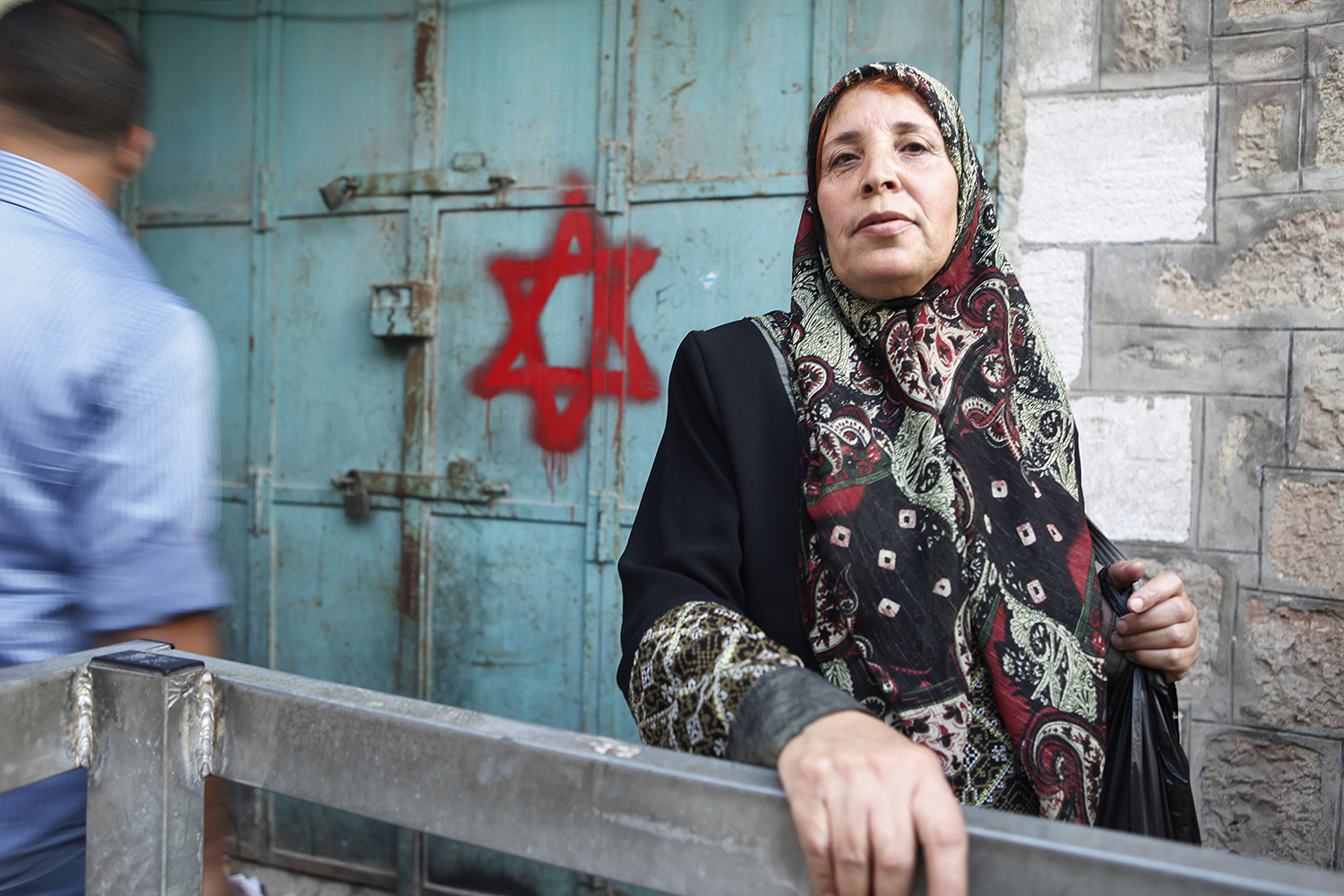 6 A Palastinian woman stands by a building in Herbron, which has been marked with the Jewish cross to sybolise Jewish ownership, West Bank .jpg