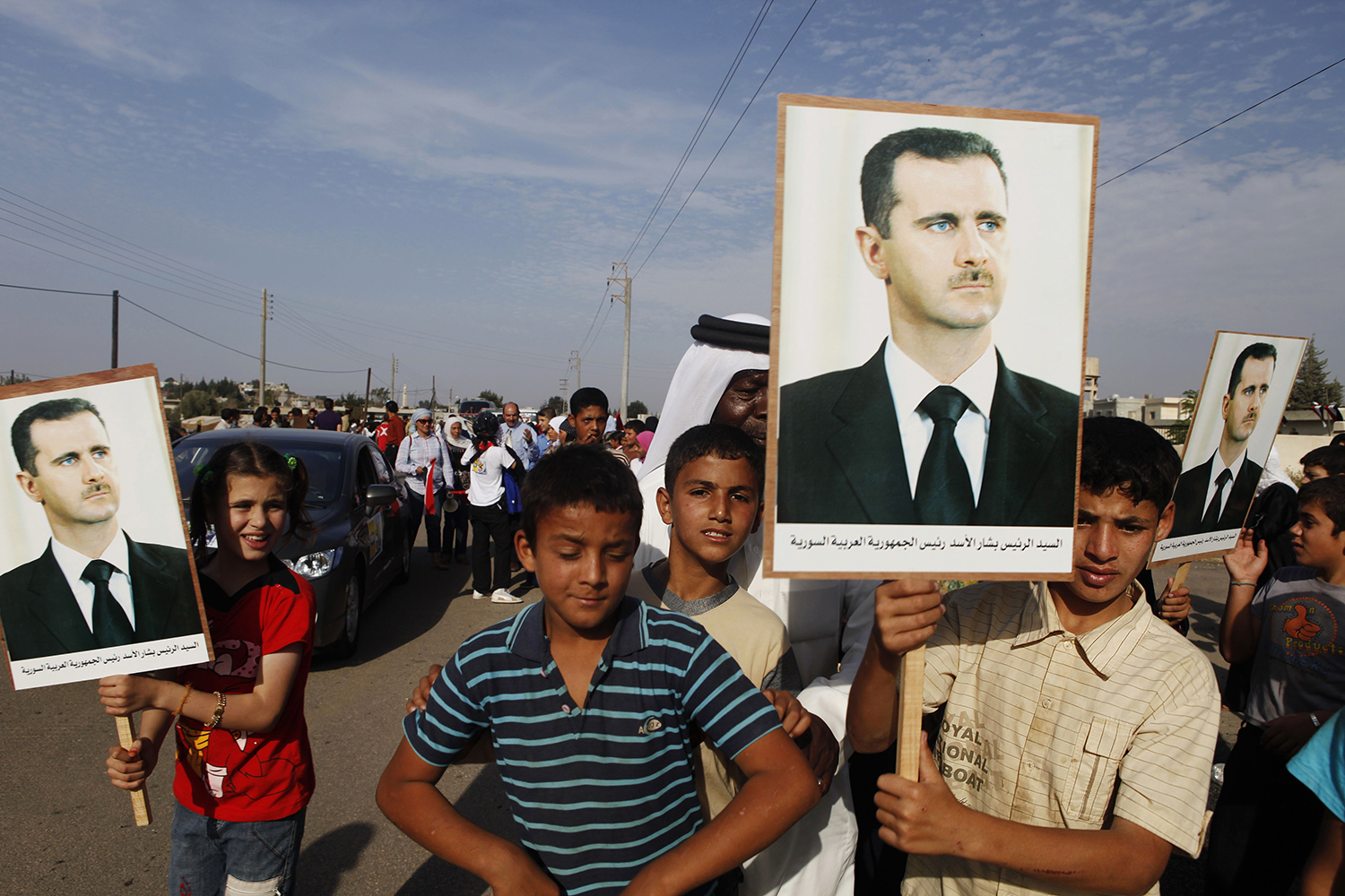 15 Children hold placards of President Asad, to welcome foreigners under supervision from state police, Darra, Syria. jpg