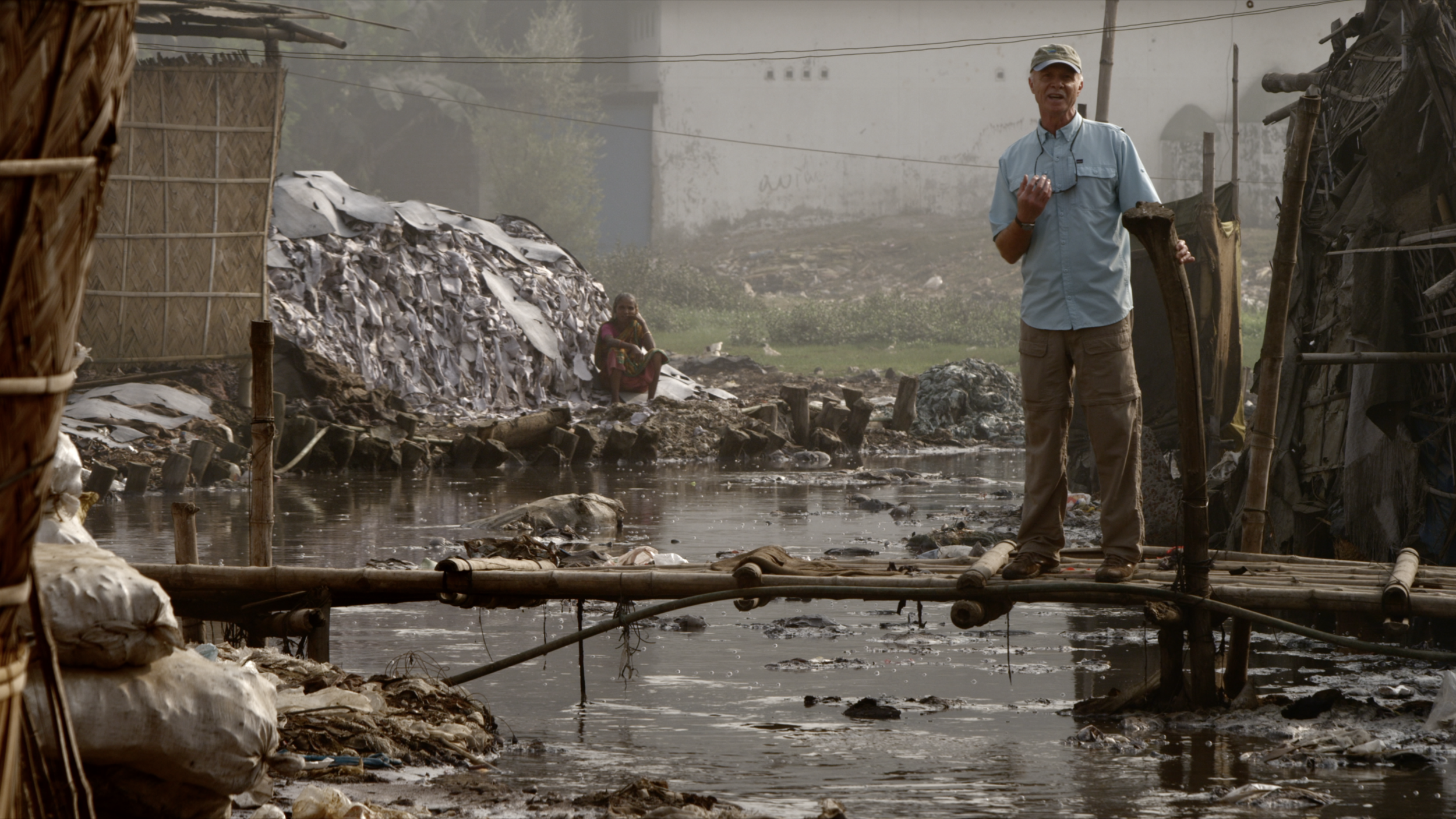 International river conservationist Mark Angelo stands above a river heavily polluted by a clothing manufacturer.