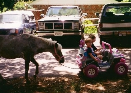 Ashley and Matt in their Jeep leading their pony Coco