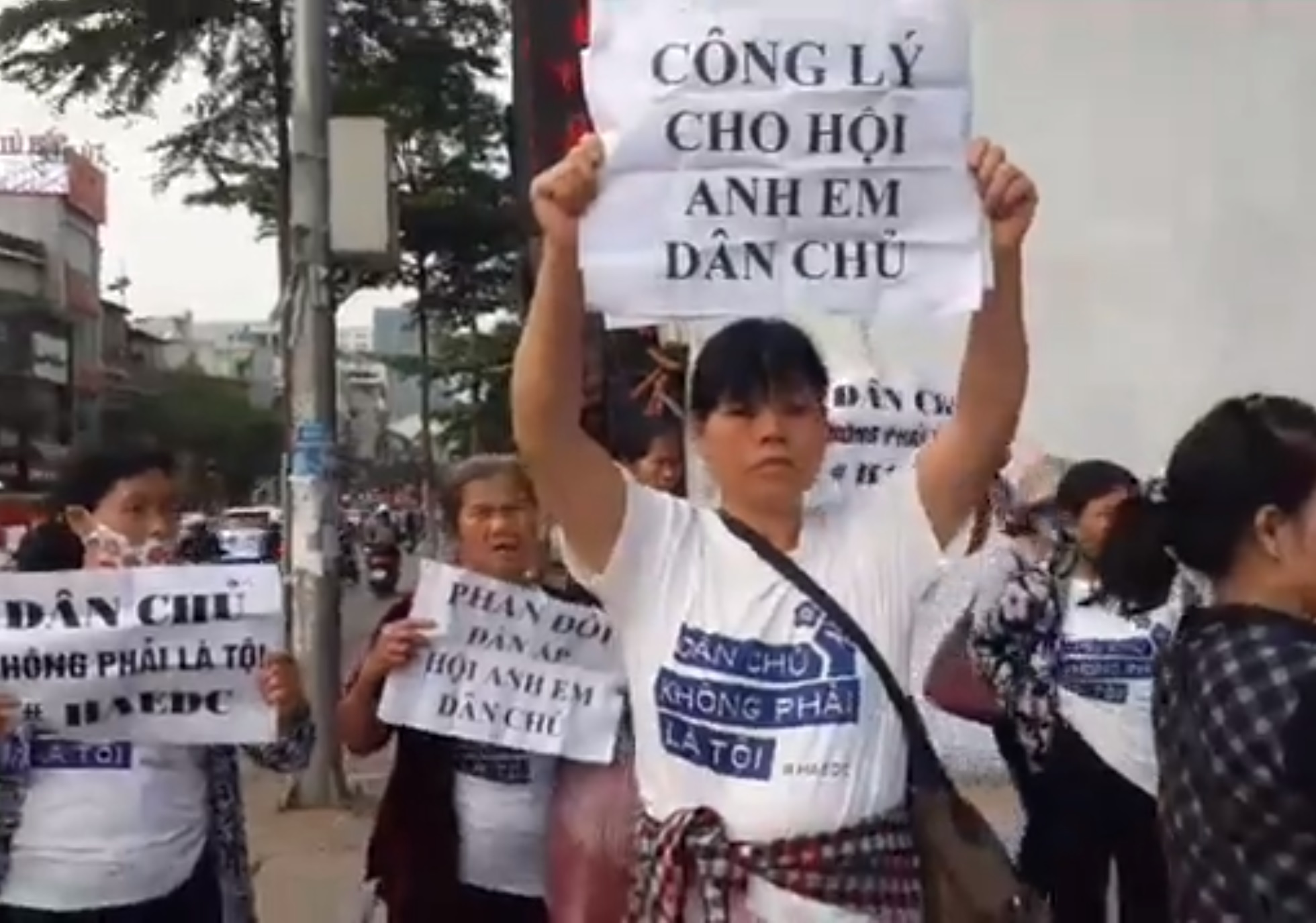 """Cấn Thị Thêu (center), a prominent land rights activist,  holds a sign that reads, """"  Justice for the Brotherhood for Democracy."""" (Photo: Screen grab, Facebook  Trịnh Bá Tư )"""