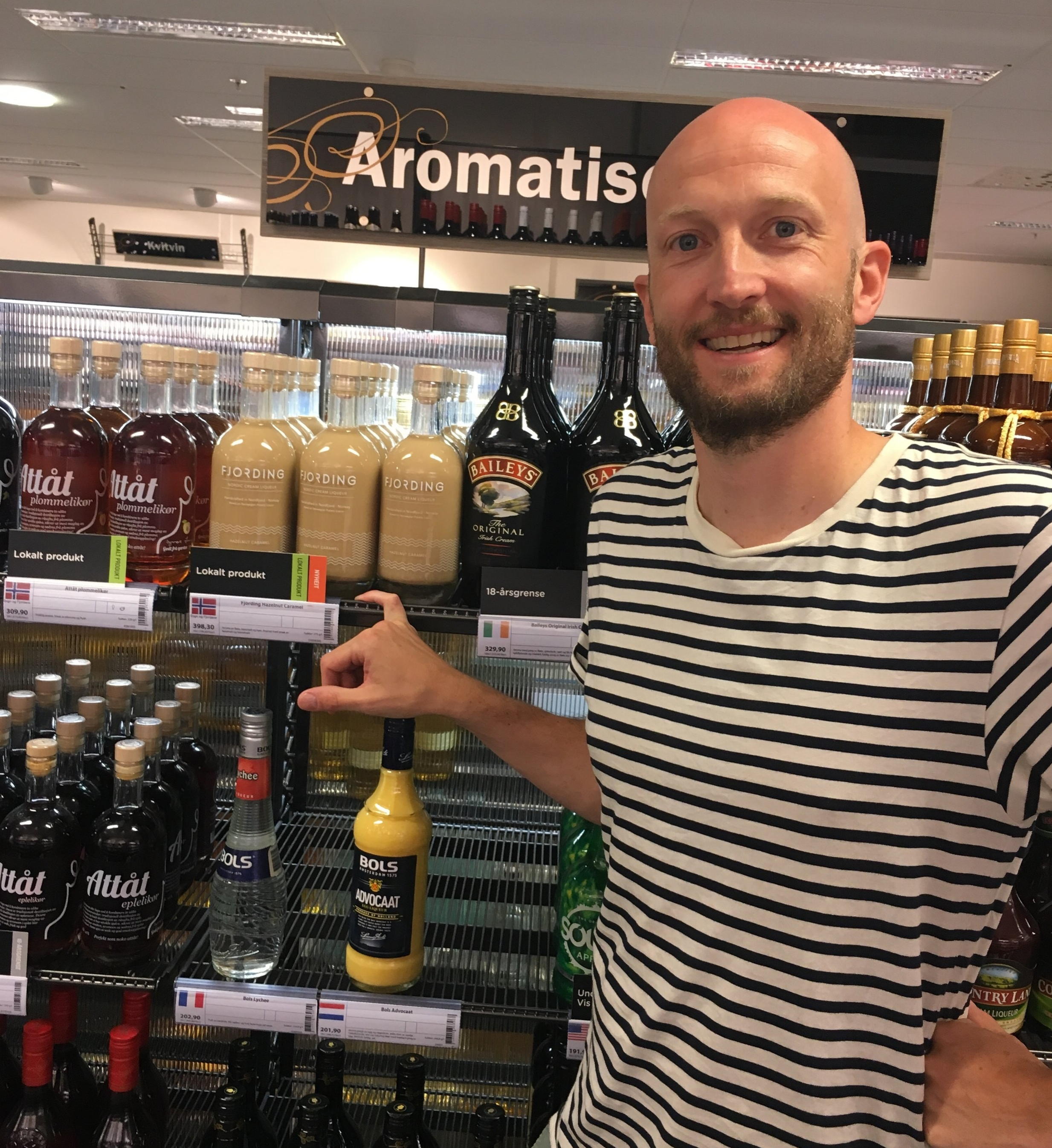 Me posing in front of a well balanced liqueur shelf at Vinmonopolet Nordfjordeid.