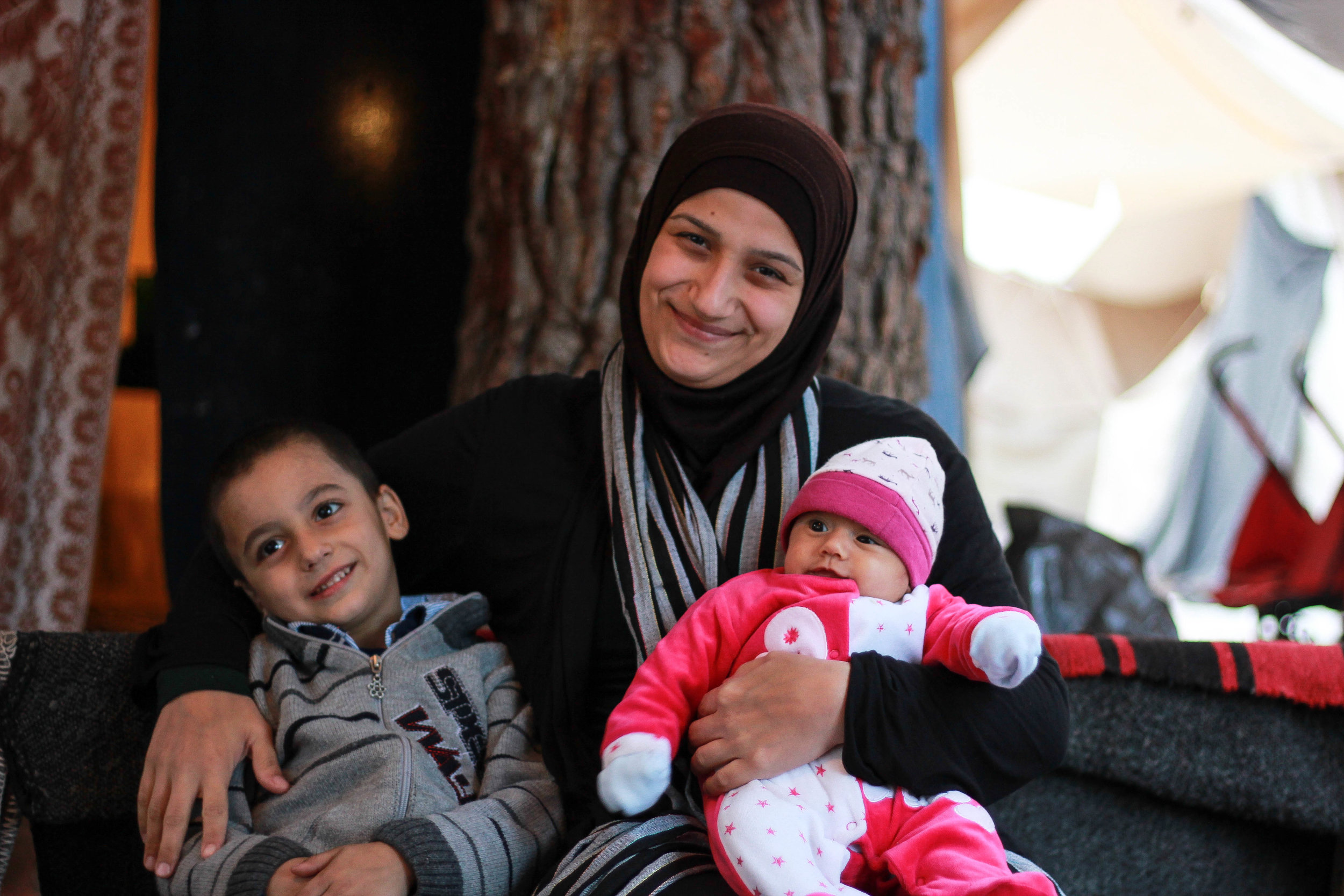 """Hala Baroud, 28 years old, from Latakia, Syria / Photo: Shayanne Gal   """"When we arrived at the refugee camp, I cried and cried. 'How can we live here, in tents, in the middle of a forest, when it is so cold and muddy?' I told my husband. It took me two months to get used to the idea that this was our life now, that we are truly refugees.""""   """"One of the most difficult things for me here is the feeling that I have lost my family, my husband, and I have lost my son here. We used to have it all, but now we depend on the volunteers for food, for clothes, for everything. We have to ask for the smallest things, like some washing powder - it is humiliating. My son asks me for something but I cannot buy it for him, so he asks the volunteers instead. He has become a beggar, like a street child, and I cannot stand to see that. I feel like I have lost him to this place."""""""