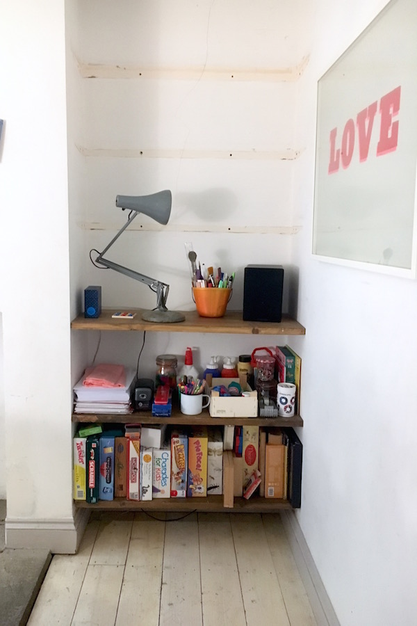 An 'after' photo of a clean, decluttered and less filled with 'stuff' bookcase in a family home.