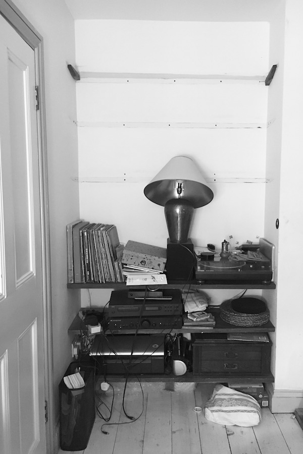 A black and white photo of an untidy, disorganised and chaotic bookshelf full of technology, records and equipment.